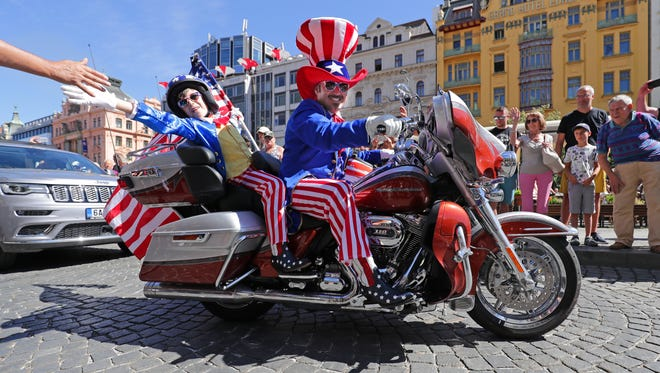 A boy reaches to high-five a parade watcher in Prague during the European portion of Harley-Davidson's 115th anniversary celebration in July.