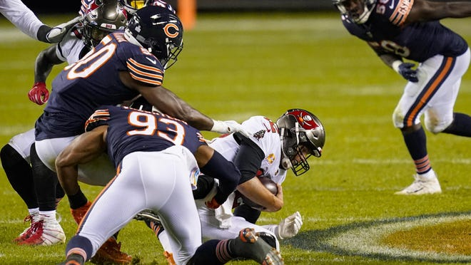 Tampa Bay Buccaneers quarterback Tom Brady (12) is sacked by Chicago Bears outside linebacker Barkevious Mingo (50) and linebacker James Vaughters (93) in the second half on Thursday in Chicago.