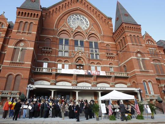 A crowd gathers in front of Cincinnati's Music Hall in Over-the-Rhine in 2011 to pay respects to Carl H. Lindner, Jr. as his funeral procession passes by.