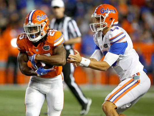 FILE - In this April 17, 2017, file photo,  Florida running back Jordan Scarlett (25) takes the handoff from quarterback Feleipe Franks (13) during an spring NCAA college football game in Gainesville, Fla. Seven suspended Florida players, including Callaway, are entering a pretrial intervention program that could result in the dismissal of felony credit card fraud charges. (Brad McClenny/The Gainesville Sun via AP, File)