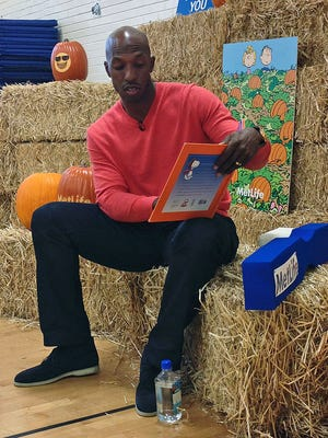 """Retired NBA basketball player Chauncey Billups reads """"It's the Great Pumpkin, Charlie Brown"""" to students at Fairview Elementary in Denver on Monday, Oct. 27, 2014. The NBA season is about to tip off and for the first time in nearly two decades, Billups won't be taking the court."""