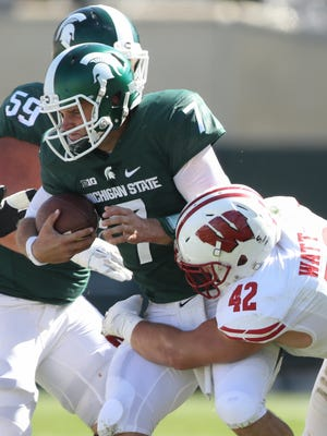 Michigan State Spartans QB Tyler O'Connor is sacked by the Wisconsin Badgers' T.J. Watt during second half action Saturday, September 24, 2016 at Spartan Stadium in East Lansing.