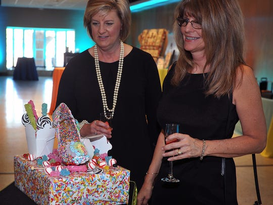 In this file photo, Tracie Kocher, left, and Debra Kelley check out a candy-covered shoe sculpture by Hoegger Communications at the High Heels for Hot Meals event at The Forum. The annual party raises money for The Kitchen and Meals On Wheels.