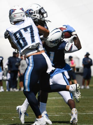 Titans safety Da'Norris Searcy (21) pulls in an interception over wide receiver Eric Decker (87) during training camp practice Monday, July 31, 2017, at Saint Thomas Sports Park.