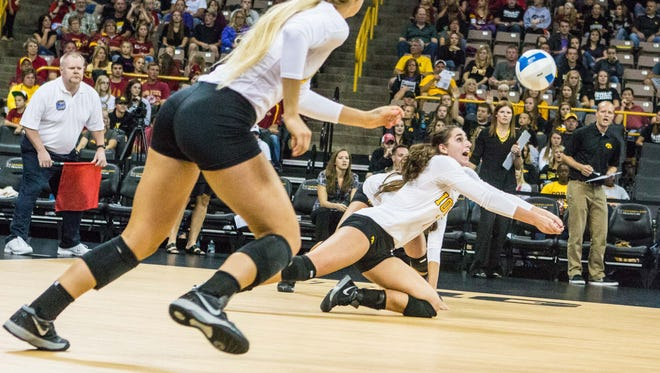 Iowa's Alex Lovell, right, returns a volley against Iowa State on Sept. 21, 2013, at Carver-Hawkeye Arena in Iowa City. Lovell is a senior on this year's Iowa squad.