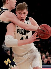 Purdue center Isaac Haas (44) drives against Michigan center Jon Teske (15) during the first half of the Big Ten Conference tournament championship NCAA college basketball game, Sunday, March 4, 2018, in New York. (AP Photo/Julie Jacobson)