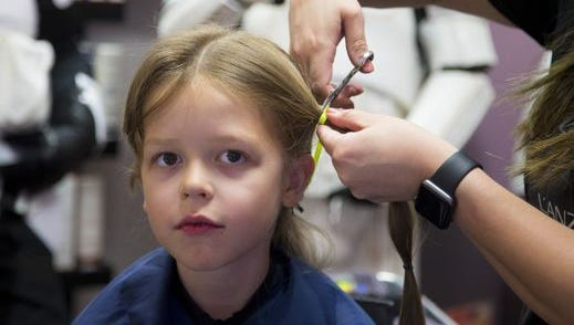 Cassie Tautimez, Pure Salon & Spa hair stylist, cuts 7-year-old Ray Decker's hair to donate to Wigs for Kids.