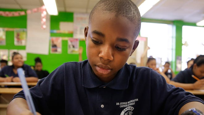 Samuel Coffey, 13, a 7th grade student at George Carver Academy, which is part of Milwaukee Public Schools, reviews math problems, while in class on Feb. 24. Carver Academy students have been wearing uniforms for the past four years.