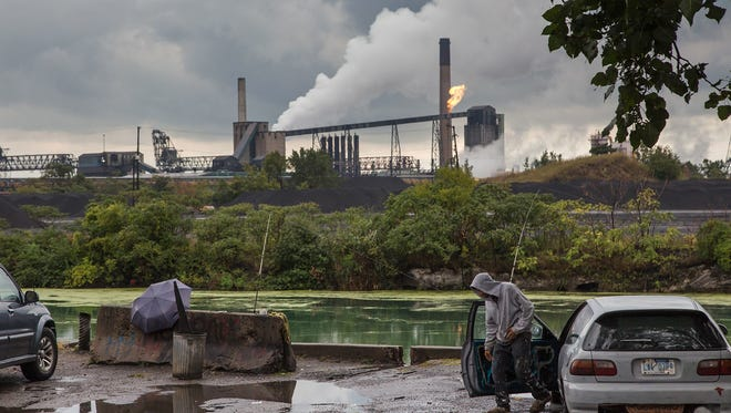 Freddy Gutierrez of Detroit gets out of his car to check his line while fishing along the Rouge River overlooking mounds of coal on Zug Island Tuesday Aug. 29, 2017.