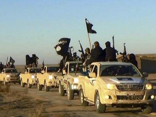 Islamic State group militants hold up their weapons