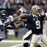 New Orleans Saints quarterback Drew Brees (9) drops back to pass under pressure from Jacksonville Jaguars defensive end Andre Branch (90) in the first half of Sunday's game.