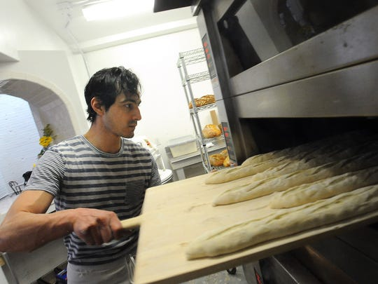 David Napolitano slides loaves of baguettes into the oven at Breadico on Tuesday, Feb. 10, 2015.