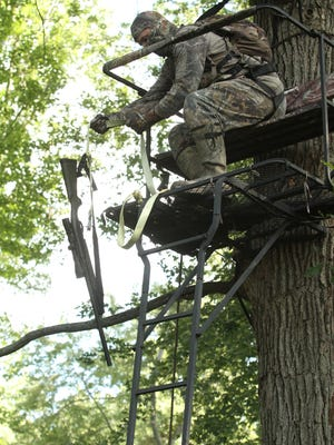After climbing the tree stand ladder and strapping himself to the tree via a body harness, hunter Corey Woody raises his firearm from ground level using a haul line which greatly reduces the chance of an accidental discharge.