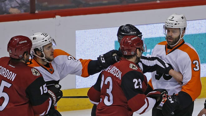 Coyotes' players retaliate after Flyers' Radio Gudas boarded Shane Doan during the second period at Gila River Arena on Saturday, March 26, 2016.