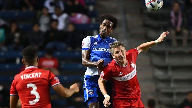 Chicago Fire midfielder Bastian Schweinsteiger (heads the ball against FC Dallas forward Atiba Harris.