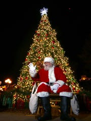 Santa Claus waves to children and parents during the Christmas Tree Lighting event in downtown Anderson.