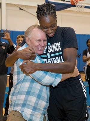 WNBA star Tina Charles hugs Dan Carlson, whose life was saved by an AED provided by her foundation.