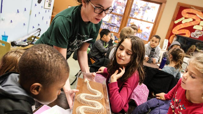 Naturalist Rachel McGovern shows children a snake skeleton during the Kids' Nature Fest: Reptiles and Amphibians at the Great Swamp Outdoor Education Center in Chatham