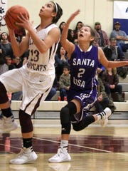Cassie Vickery, left, attempts a lay-up while being defended by Sharmaine Benally.