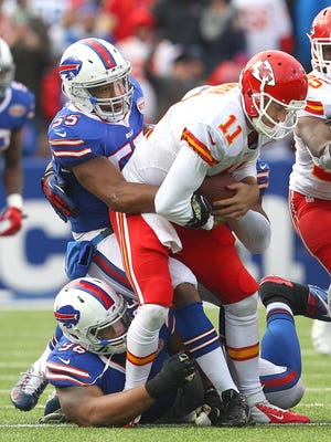Chiefs Alex Smith is sacked by Bills Jerry Hughes (55) and Stefan Charles (96).