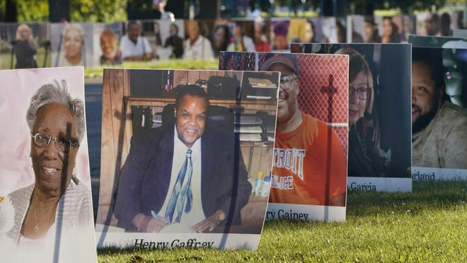 Some of the nearly 900 large poster-sized photos of Detroit victims of COVID-19 are displayed, Monday, Aug. 31, 2020 on Belle Isle in Detroit. Families have a chance to take one last public look at their lost loved ones in the nation's first citywide memorial to honor victims of the pandemic. Mourners will join 14 consecutive funeral processions to drive past the photos of their loved ones staked around the island.