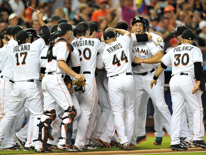 Miami Marlins players celebrate a walk-off wild pitch that sealed pitcher Henderson Alvarez's no-hitter against the Detroit Tigers at Marlins Ballpark.