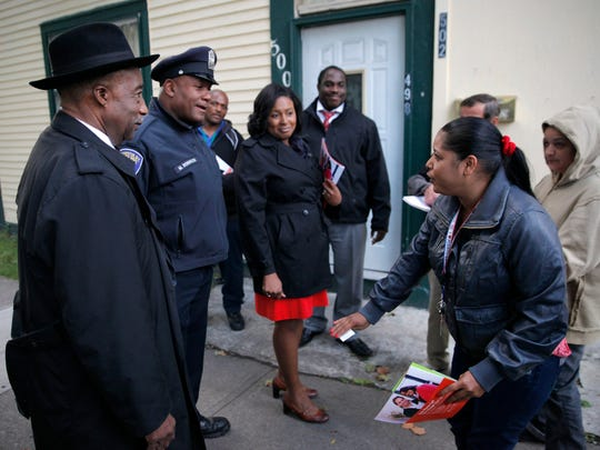Clergy on Patrol, with Rev. Roosevelt Dixon, left, Rochester Police School Resources Officer Moses Robinson and Mayor Lovely Warren talk with Mildred Perez, right, on Central Ave.