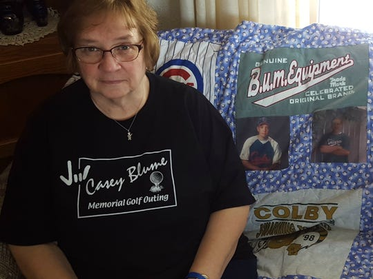 Ruth Blume sits with a quilt made from her son's old