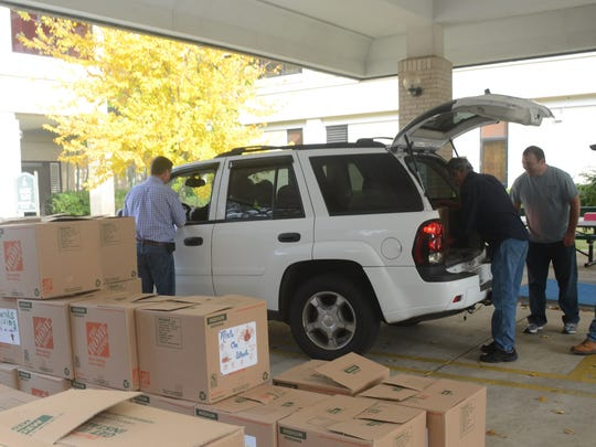 Calvary Baptist Church members and volunteers with the church's Mission CenLa program load Thanksgiving boxes into waiting cars Saturday. One hundred boxes were delivered to needy families by church members.