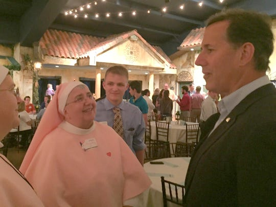 Former U.S. Sen. Rick Santorum talks with Sister Maryann Francis and Sister Mary Lucy, both of Omaha, who are members of a religious community known as Daughters of the Eternal Father, during a campaign appearance Thursday night in Glenwood in western Iowa.