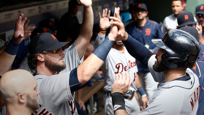 Detroit Tigers' J.D. Martinez, right, is congratulated by teammates after hitting a two-run home run against the Texas Rangers during the seventh inning of a baseball game Sunday, Aug. 14, 2016, in Arlington, Texas.