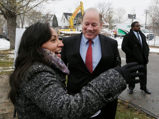Detroit Mayor Mike Duggan listens to Detroit City Council member Raquel Castaneda-Lopez prior to announcing Tuesday Nov. 24, 2015 that the city is using $750k in funds received from State's acquisition of city land for new international bridge to remove blighted properties in the Delray neighborhood.