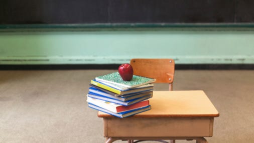 Stack of school books and apple on desk in empty classroom