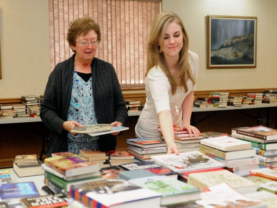 In this November 2016 photo, Clovis-Carver Public Library circulation assistants Wanda Walters, left, and Jessica Thron add books to be sold at a book sale at the library in Clovis, N.M. In a shooting rampage Monday, Aug. 28, 2017, Walters was killed and Thron was injured. One other person died and a few others were wounded. Authorities on Tuesday identified the accused gunman as Nathaniel Jouett, a 16-year-old high school student.