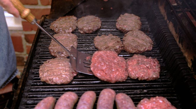 A man grills hamburgers and sausages in Decatur, Ga.