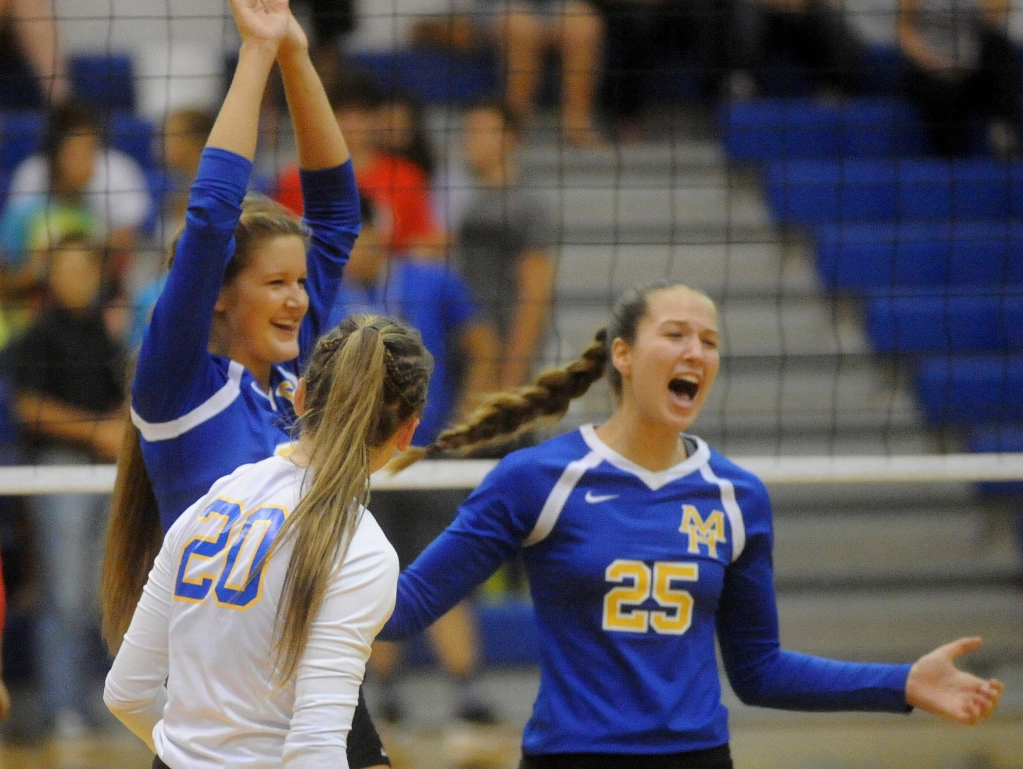 Mountain Home seniors Katie Wehmeyer and McKenzie Brannon (20) and sophomore Maly Tabor (25) celebrate a point during the Lady Bombers' five-set victory over Marion on Thursday night at The Hangar.