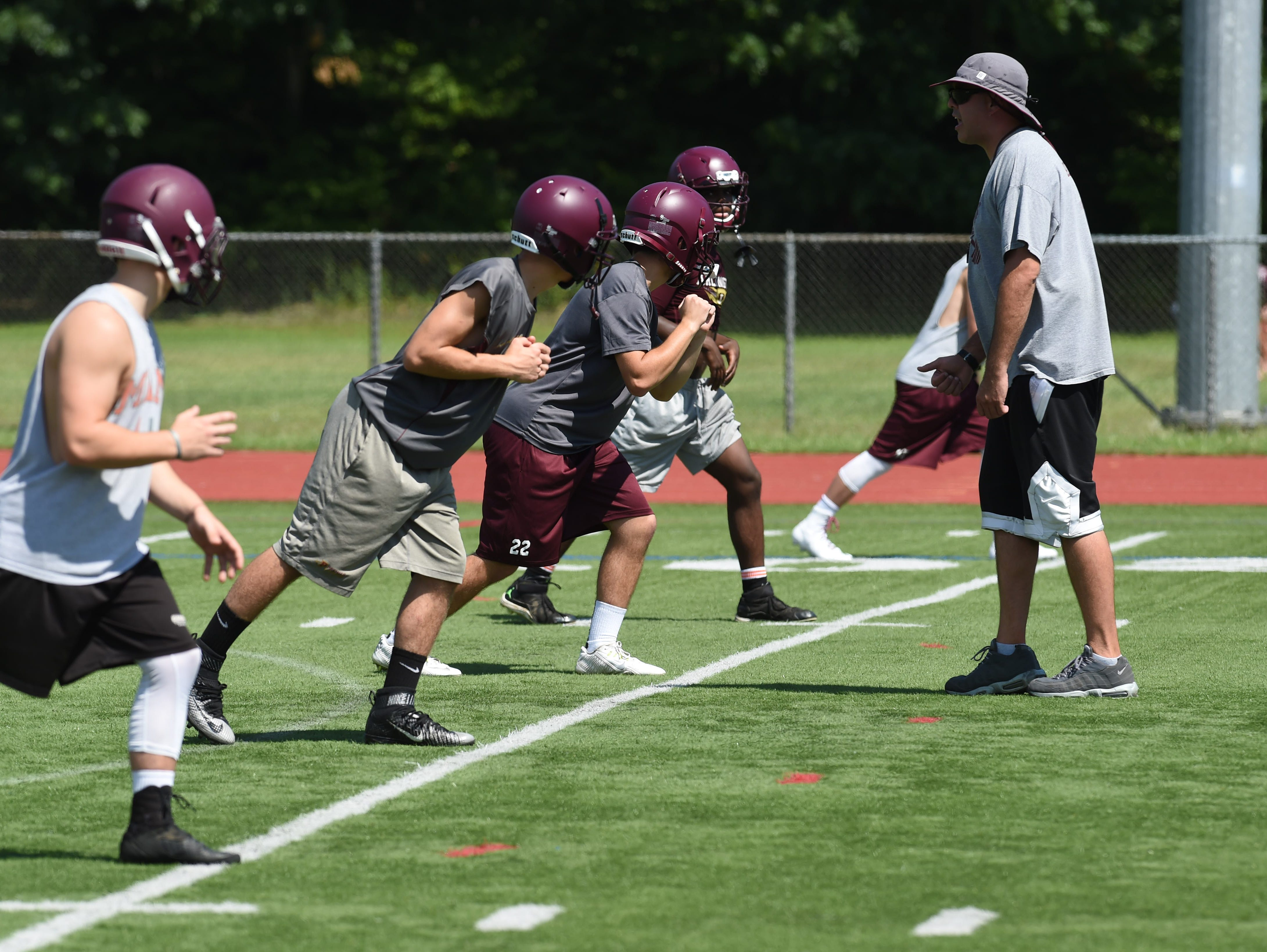 Jim Killian, assistant varsity football coach at Arlington High School, goes over the correct stance with a group of wide receivers during preseason football practice.