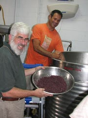 Sam Calagione and Patrick McGovern add salivated Peruvian red corn cakes to the kettle at Dogfish Head, a Rehoboth Beach, Delaware, brewpub, on their way to re-creating their Chicha.