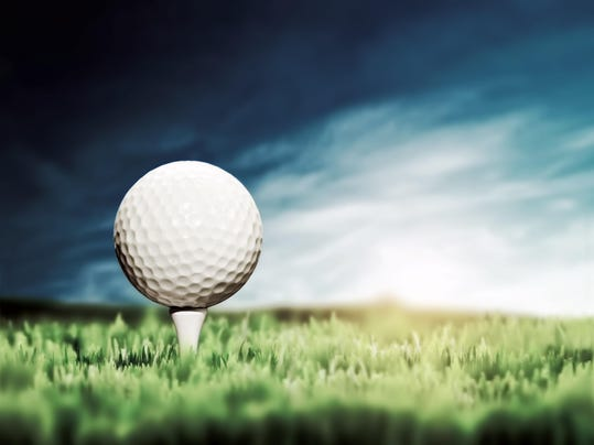 Close-up of golf ball placed on white tee in grass