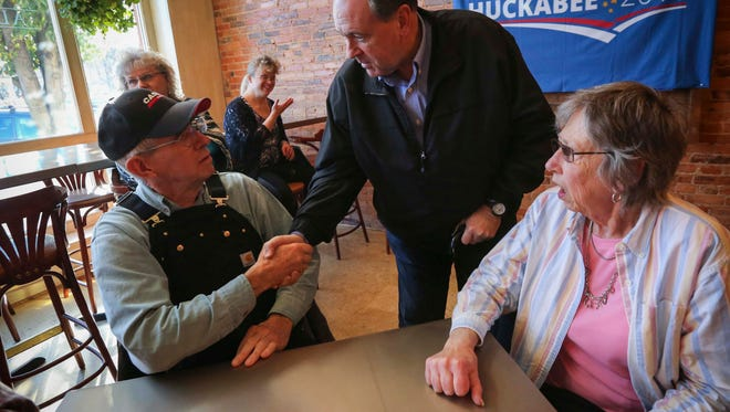 Republican presidential hopeful former Arkansas governor Mike Huckabee shakes hands with Tom Kaldenberg, right, of Albia, at the Albia Brewing Co., Thursday Nov. 19, 2015.