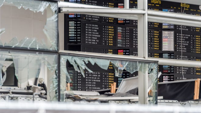 An arrivals and departure board is seen behind blown-out windows March 23, 2016, at Zaventem Airport in Brussels. Airport officials said the airport would reopen with limited service April 3, 2016.