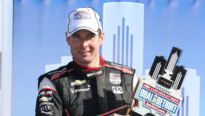 Driver Will Power holds the winner's trophy after his victory at Belle Isle Park on Saturday.