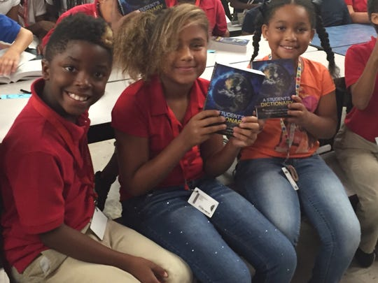 Colonial Elementary School students Dereon Thomas, Gaby Wilson and Joice Taylor hold up the dictionaries they received Friday from the Lee County Rotarians. The 13 clubs handed out more than 10,200 dictionaries to the district's third-grade students.