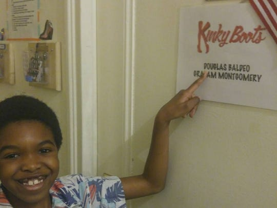 Douglas Baldeo shows off a sign with his name