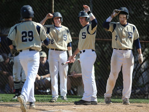 Salesianum's Zachary Miller (left) is greeted at the plate by (from second from left) Sean Mazzio, Matt Taylor and Matt Shackleford after his three-run homer in the third inning in Salesianum's 17-7, six inning win at Charter School of Wilmington, Tuesday, May 6, 2014.