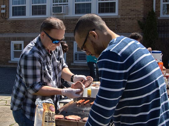 Members of Dunellen's Community Bible Church, Gregory Momat and Timon Jackson, prepare food for a community program at the church. The program reflects the growing community presence pastor Noah Lang has been encouraging in the church.