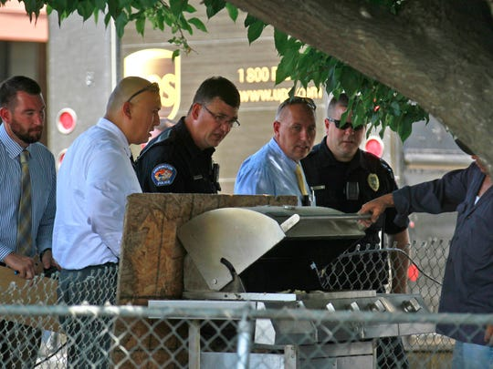 Farmington Police Department officers and detectives talk with a Royal Mobile Home Park resident, at right, while investigating the stabbing of a delivery driver on Wednesday.