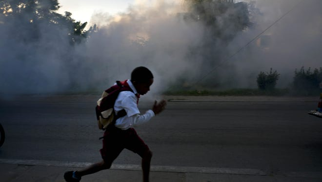 A student runs past fumigation fog, sprayed to kill Aedes aegypti mosquitos, in Pinar del Rio, Cuba. Authorities are fumigating in an attempt to prevent the spread of Zika, chikungunya and dengue.