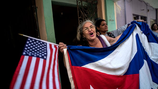 Maria Castro shouts slogans celebrating the visit by U.S. President Barack Obama and the reconciliation of the Cuban and American peoples, while holding a Cuban and an American flag, near the Grand Theater of Havana, where President Obama delivered a speech, in Havana, Cuba,Tuesday,
