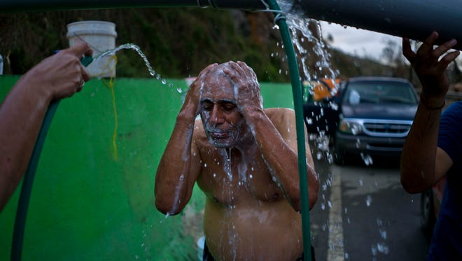 People affected by Hurricane Maria bathe in water piped from a creek in the mountains, in Naranjito, Puerto Rico, Thursday, Sept. 28, 2017. Residents of the area drive to the pipes to bathe because they were left without water supplies by the damage caused by Hurricane Maria. The pipe was set up by a neighbor who ran it from a creek in his property to the side of the road in order to help those left without water. (AP Photo/Ramon Espinosa)